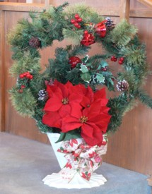 Other decorations include a poinsettia, more evergreen, and holly and berries.