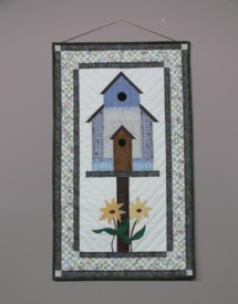 A hand-crafted quilted hanging depicting home and nature.